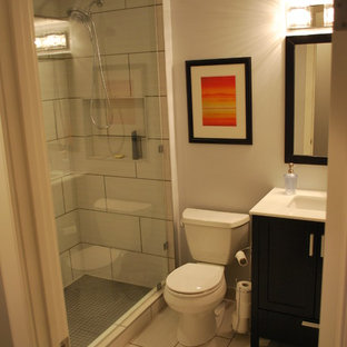 This is an example of a small modern 3/4 bathroom in Calgary with shaker cabinets, dark wood cabinets, an alcove shower, a two-piece toilet, beige tile, porcelain tile, beige walls, laminate floors, an undermount sink, solid surface benchtops, beige floor and a hinged shower door.
