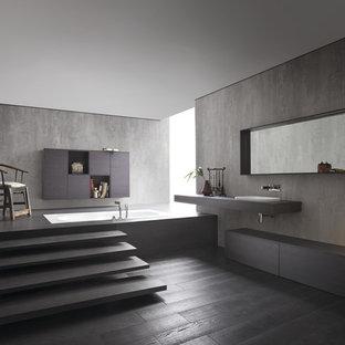 Ispirazione per una piccola stanza da bagno con doccia moderna con lavabo integrato, ante lisce, ante in legno bruno, vasca sottopiano, WC monopezzo, piastrelle bianche, piastrelle in ceramica, pareti grigie e parquet scuro