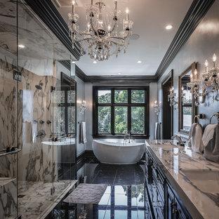 Klassisches Badezimmer mit profilierten Schrankfronten, schwarzen Schränken, freistehender Badewanne, bodengleicher Dusche, schwarz-weißen Fliesen, grauer Wandfarbe, Unterbauwaschbecken, schwarzem Boden, Falttür-Duschabtrennung und weißer Waschtischplatte in Milwaukee