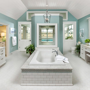Example of a coastal master white tile and subway tile drop-in bathtub design in Milwaukee with white cabinets and blue walls