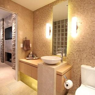 Modelo de cuarto de baño principal, contemporáneo, grande, con armarios con paneles lisos, puertas de armario de madera clara, sanitario de una pieza, baldosas y/o azulejos de terracota, paredes multicolor, suelo de piedra caliza, lavabo sobreencimera y encimera de madera