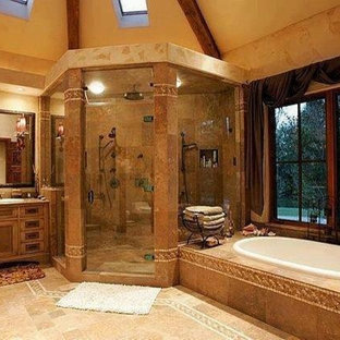 Inspiration for a large mediterranean ensuite bathroom in New York with recessed-panel cabinets, dark wood cabinets, a built-in bath, an alcove shower, beige tiles, brown tiles, ceramic tiles, beige walls, ceramic flooring, a built-in sink, granite worktops, brown floors and a hinged door.