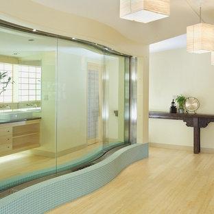 Modelo de cuarto de baño grande con lavabo sobreencimera, armarios abiertos, puertas de armario de madera clara, encimera de ónix, baldosas y/o azulejos azules, baldosas y/o azulejos de vidrio laminado, paredes beige y suelo de madera clara