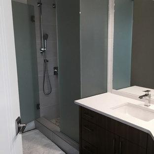 Modelo de cuarto de baño infantil, tradicional renovado, de tamaño medio, con armarios con paneles lisos, puertas de armario de madera en tonos medios, ducha esquinera, sanitario de una pieza, baldosas y/o azulejos grises, baldosas y/o azulejos de porcelana, paredes blancas, suelo de linóleo, lavabo bajoencimera, encimera de cuarzo compacto, suelo gris y ducha con puerta con bisagras