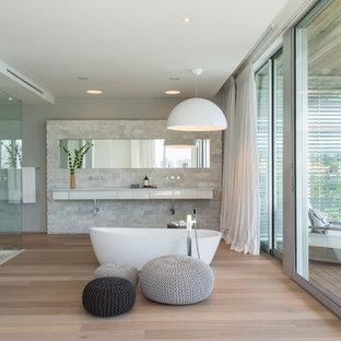 Diseño de cuarto de baño principal, actual, grande, con armarios con paneles lisos, puertas de armario blancas, bañera exenta, suelo de madera clara, paredes blancas y suelo marrón