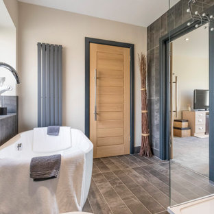 Inspiration for a large contemporary ensuite bathroom in Sussex with a freestanding bath, a corner shower, grey tiles, porcelain tiles, beige walls, grey floors and a hinged door.
