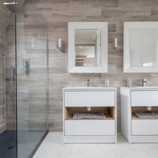 Inspiration for a large contemporary grey and white shower room bathroom in Sussex with flat-panel cabinets, white cabinets, a corner shower, beige tiles, white walls, white floors, an open shower, white worktops, double sinks and a built in vanity unit.