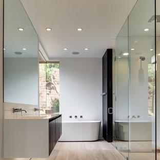 Modern inredning av ett badrum med dusch, med släta luckor, skåp i mörkt trä, ett fristående badkar, en kantlös dusch, vita väggar, ett integrerad handfat, beiget golv och dusch med gångjärnsdörr