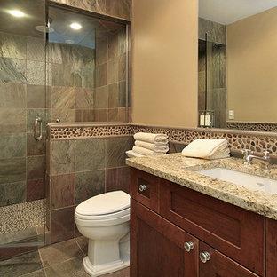 Diseño de cuarto de baño con ducha, tradicional, grande, con armarios estilo shaker, puertas de armario de madera en tonos medios, ducha empotrada, sanitario de una pieza, baldosas y/o azulejos multicolor, baldosas y/o azulejos de pizarra, paredes beige, suelo de pizarra, lavabo bajoencimera y encimera de granito
