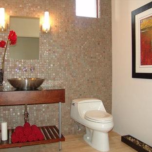Diseño de cuarto de baño ecléctico, pequeño, con puertas de armario de madera en tonos medios, sanitario de una pieza, baldosas y/o azulejos en mosaico, paredes blancas, suelo de madera clara, lavabo sobreencimera, encimera de vidrio y suelo marrón