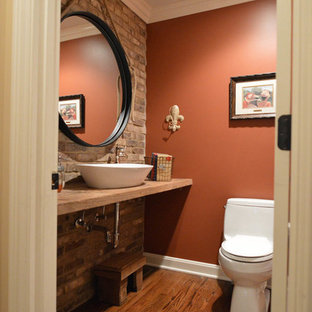 Kleines Rustikales Badezimmer mit Toilette mit Aufsatzspülkasten, oranger Wandfarbe, braunem Holzboden, Waschtisch aus Holz und Aufsatzwaschbecken in Louisville