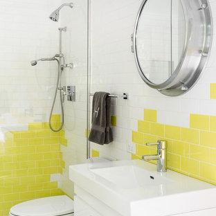 Cette photo montre une salle de bain tendance pour enfant avec un placard à porte plane, des portes de placard blanches, un carrelage blanc, un carrelage jaune, un carrelage métro et un lavabo intégré.