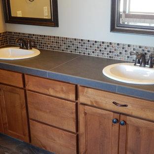 Mittelgroßes Rustikales Badezimmer En Suite mit Einbauwaschbecken, Schrankfronten mit vertiefter Füllung, braunen Schränken, gefliestem Waschtisch, grauen Fliesen, Porzellanfliesen, beiger Wandfarbe und Porzellan-Bodenfliesen in Seattle