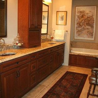 ニューオリンズの中サイズのトラディショナルスタイルのおしゃれなマスターバスルーム (レイズドパネル扉のキャビネット、茶色いキャビネット、コーナー型浴槽、ベージュの壁、セラミックタイルの床、オーバーカウンターシンク、御影石の洗面台、ベージュの床) の写真