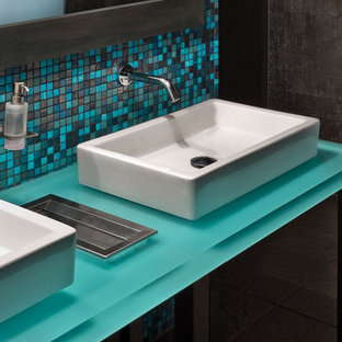 Foto de cuarto de baño principal, bohemio, de tamaño medio, con bañera encastrada, ducha doble, losas de piedra, suelo de travertino, baldosas y/o azulejos azules, paredes grises, encimera de vidrio y encimeras azules