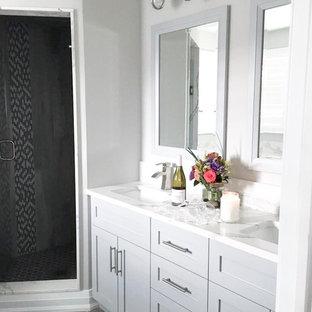Immagine di una piccola stanza da bagno padronale minimal con ante in stile shaker, ante grigie, vasca ad angolo, doccia ad angolo, WC monopezzo, pareti grigie, pavimento in laminato, lavabo sottopiano, top in quarzo composito, pavimento grigio, porta doccia a battente e top bianco