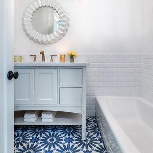 Esempio di una stanza da bagno eclettica di medie dimensioni con vasca da incasso, piastrelle bianche, piastrelle diamantate, pareti bianche, pavimento in gres porcellanato, lavabo sottopiano, top in quarzo composito, pavimento blu, porta doccia a battente e top grigio