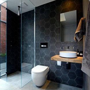 Modern inredning av ett mellanstort badrum med dusch, med öppna hyllor, skåp i ljust trä, en öppen dusch, en toalettstol med hel cisternkåpa, svart kakel, marmorkakel, svarta väggar, betonggolv, ett fristående handfat, träbänkskiva, grått golv och med dusch som är öppen