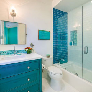 Inspiration for a contemporary blue tile and mosaic tile ceramic floor alcove bathtub remodel in Orange County with furniture-like cabinets, blue cabinets, a one-piece toilet, white walls, an undermount sink and engineered quartz countertops