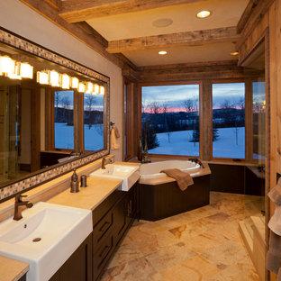 Immagine di una grande stanza da bagno padronale stile rurale con ante in stile shaker, ante in legno bruno, vasca ad angolo, piastrelle beige, pareti beige e lavabo rettangolare