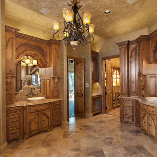 Example of a mid-sized tuscan master beige tile and ceramic tile ceramic tile and beige floor alcove shower design in Dallas with raised-panel cabinets, medium tone wood cabinets, a two-piece toilet, beige walls, a vessel sink, granite countertops and a hinged shower door