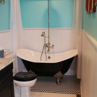 Modelo de cuarto de baño principal, tradicional, de tamaño medio, con armarios con paneles empotrados, puertas de armario negras, bañera con patas, combinación de ducha y bañera, sanitario de dos piezas, paredes azules, suelo de baldosas de porcelana, lavabo bajoencimera, suelo multicolor y ducha con cortina
