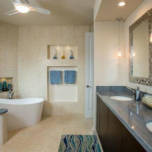 ハワイの中サイズのトランジショナルスタイルのおしゃれなマスターバスルーム (フラットパネル扉のキャビネット、濃色木目調キャビネット、置き型浴槽、ベージュのタイル、ライムストーンタイル、ベージュの壁、ライムストーンの床、アンダーカウンター洗面器、珪岩の洗面台、ベージュの床、青い洗面カウンター) の写真