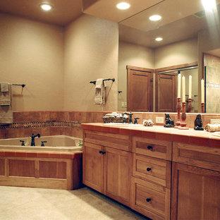 Großes Klassisches Badezimmer En Suite mit Einbauwaschbecken, Schrankfronten mit vertiefter Füllung, hellbraunen Holzschränken, gefliestem Waschtisch, Eckbadewanne, farbigen Fliesen, Keramikfliesen, beiger Wandfarbe und Keramikboden in Sonstige