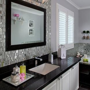 Cette photo montre une grand salle de bain principale moderne avec un placard avec porte à panneau surélevé, des portes de placard blanches, une baignoire posée, des carreaux de miroir, un mur gris, un sol en carrelage de porcelaine, un lavabo encastré, un plan de toilette en granite et un sol noir.
