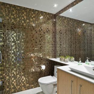 Immagine di una stanza da bagno con doccia moderna di medie dimensioni con ante lisce, ante in legno chiaro, doccia ad angolo, WC monopezzo, piastrelle marroni, piastrelle in metallo, lavabo a bacinella, pavimento grigio e porta doccia a battente