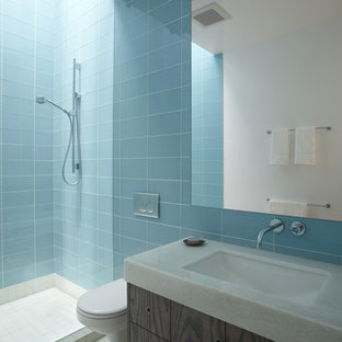 Photo of a contemporary bathroom in San Francisco with a wall-mount toilet, blue tile and glass tile.