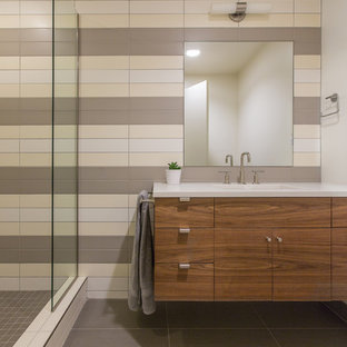 Trendy 3/4 beige tile, brown tile, gray tile and white tile gray floor doorless shower photo in Portland with flat-panel cabinets, dark wood cabinets and multicolored walls