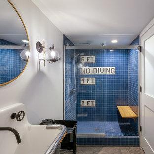 Immagine di una stanza da bagno con doccia industriale con doccia alcova, piastrelle blu, piastrelle in ceramica, pareti bianche, pavimento in cemento, lavabo sospeso, pavimento grigio e porta doccia scorrevole