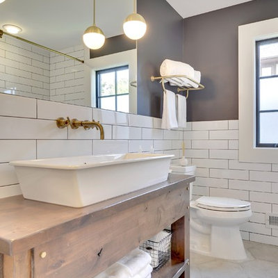 Inspiration for a transitional white tile gray floor bathroom remodel in Minneapolis with furniture-like cabinets, medium tone wood cabinets, gray walls, a vessel sink, wood countertops and brown countertops