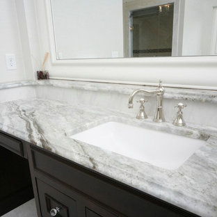 Bathroom - huge traditional gray tile and stone tile marble floor bathroom idea in Boston with an undermount sink, recessed-panel cabinets, dark wood cabinets, marble countertops, a one-piece toilet and beige walls