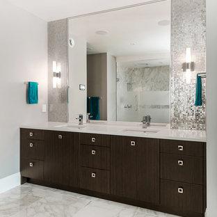 Foto di una grande stanza da bagno padronale design con lavabo sottopiano, ante lisce, ante in legno bruno, top in quarzo composito, doccia alcova, WC monopezzo, piastrelle grigie, piastrelle di vetro, pareti grigie e pavimento in marmo
