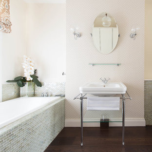 Photo of a traditional ensuite bathroom in London with grey tiles, beige walls, dark hardwood flooring, a console sink, brown floors, a built-in bath and mosaic tiles.
