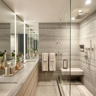 Modelo de cuarto de baño principal, moderno, de tamaño medio, con armarios con paneles lisos, puertas de armario de madera clara, ducha esquinera, sanitario de pared, baldosas y/o azulejos grises, baldosas y/o azulejos de travertino, paredes grises, suelo de travertino, lavabo bajoencimera, encimera de piedra caliza, suelo gris, ducha con puerta con bisagras y encimeras grises