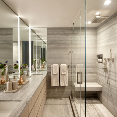Inspiration for a mid-sized modern master gray tile and travertine tile travertine floor and gray floor corner shower remodel in New York with flat-panel cabinets, light wood cabinets, a wall-mount toilet, gray walls, an undermount sink, limestone countertops, a hinged shower door and gray countertops