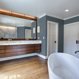 Large elegant master medium tone wood floor bathroom photo in San Francisco with an integrated sink, medium tone wood cabinets, marble countertops, a two-piece toilet and blue walls