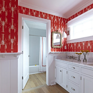 Design ideas for a large beach style kids bathroom in New York with shaker cabinets, white cabinets, a freestanding tub, a shower/bathtub combo, a two-piece toilet, red walls, light hardwood floors, an undermount sink and marble benchtops.
