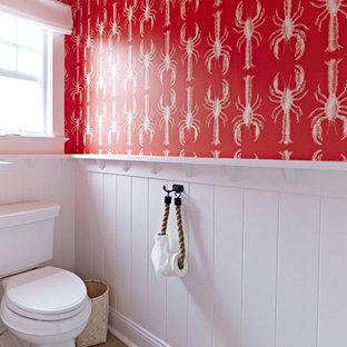 Cette image montre une grande salle de bain marine pour enfant avec un WC séparé, un mur rouge, un sol en bois clair, un lavabo encastré et un plan de toilette en marbre.