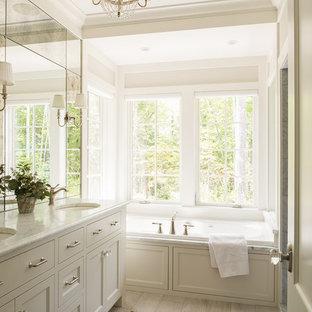 Inredning av ett maritimt en-suite badrum, med skåp i shakerstil, vita skåp, ett platsbyggt badkar, ljust trägolv och ett undermonterad handfat