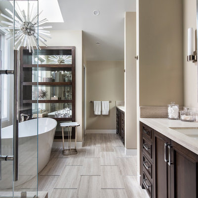 Inspiration for a mid-sized transitional master beige tile and porcelain tile porcelain tile and beige floor bathroom remodel in Orange County with beige walls, an undermount sink, a hinged shower door, recessed-panel cabinets, dark wood cabinets and beige countertops