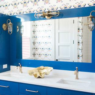 Cette image montre une salle de bain marine pour enfant avec un placard à porte plane, des portes de placard bleues, un mur multicolore, un lavabo encastré et un plan de toilette blanc.