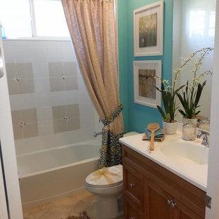 Ispirazione per una stanza da bagno con doccia costiera di medie dimensioni con lavabo integrato, ante con bugna sagomata, ante in legno chiaro, top in granito, vasca ad alcova, vasca/doccia, WC monopezzo, piastrelle multicolore, piastrelle in ceramica, pareti blu e pavimento in travertino