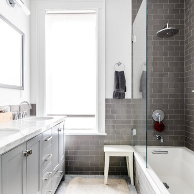 Inspiration for a transitional gray tile and subway tile drop-in bathtub remodel in New York with shaker cabinets, gray cabinets, white walls and an undermount sink