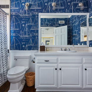 Mid-sized elegant kids' beige tile medium tone wood floor bathroom photo in Orange County with raised-panel cabinets, white cabinets, blue walls, a drop-in sink and tile countertops