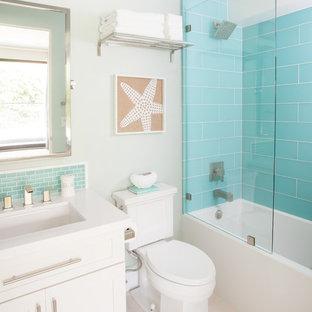 Immagine di una stanza da bagno stile marinaro con lavabo sottopiano, ante in stile shaker, ante bianche, vasca ad alcova, vasca/doccia, WC a due pezzi, piastrelle blu, piastrelle di vetro e pareti bianche