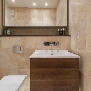 Diseño de cuarto de baño infantil, actual, pequeño, con armarios con paneles lisos, puertas de armario de madera en tonos medios, sanitario de pared, baldosas y/o azulejos beige, baldosas y/o azulejos de travertino, paredes beige, suelo de travertino, lavabo suspendido, encimera de madera y suelo beige